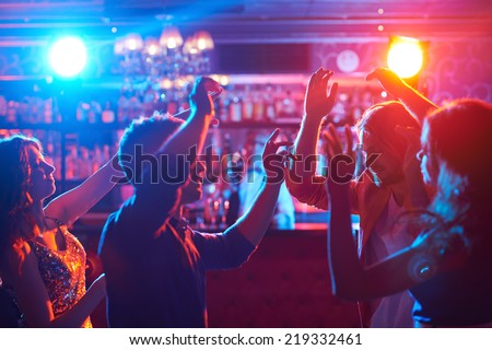 Portrait of happy friends dancing at party - stock photo