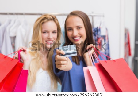 Portrait of happy friends handing a credit card - stock photo