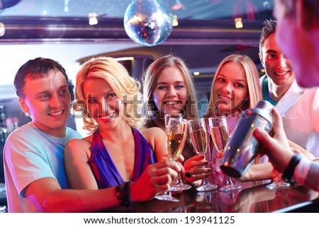 Portrait of happy friends holding glasses with cocktails and looking at barman at party