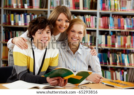 Portrait of happy friends looking at camera in library - stock photo