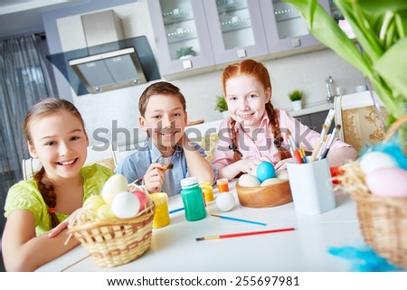 Portrait of happy friends painting eggs in the kitchen - stock photo
