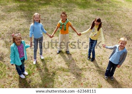 Portrait of happy friends standing on the ground in park and looking at camera - stock photo