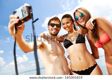 Portrait of happy friends taking photo of themselves on the beach - stock photo
