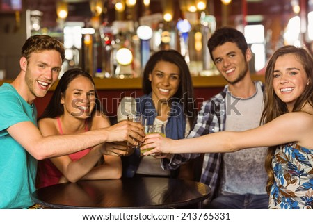 Portrait of happy friends toasting with drink and beer in a pub - stock photo