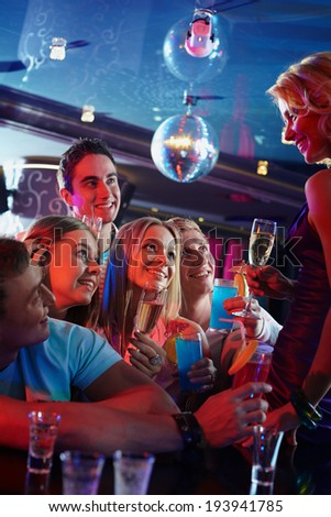 Portrait of happy friends with alcohol looking at attractive girl with glass of champagne in the bar - stock photo