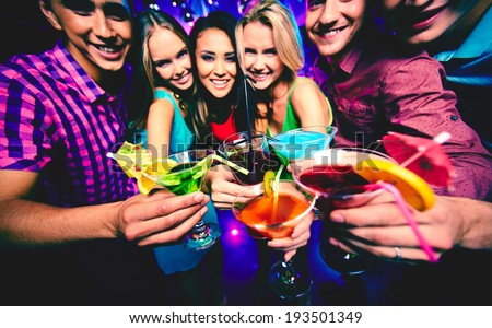 Portrait of happy friends with cocktails looking at camera at party - stock photo