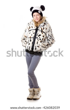 Portrait of happy funny beautiful casual teenage girl wearing winter coat and knitted panda hat, holding hands in pockets, full length, studio image, white background - stock photo