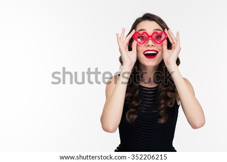 Portrait of happy funny curly young woman with retro hairstyle in red heart shaped glasses