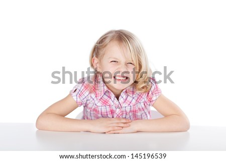 Portrait of happy funny girl at table isolated over white background - stock photo