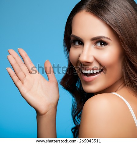 Portrait of happy gesturing smiling young beautiful woman, in white casual clothing, over blue background - stock photo