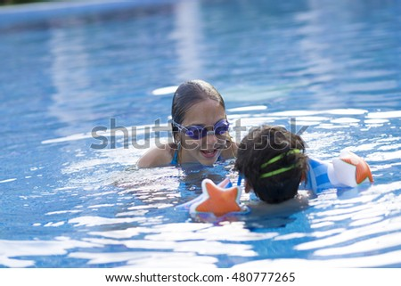 Portrait of Happy Girl and Boy Enjoying in Swimming Pool