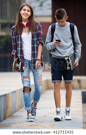 Portrait of happy girl and boy teenagers with skateboards outdoors 