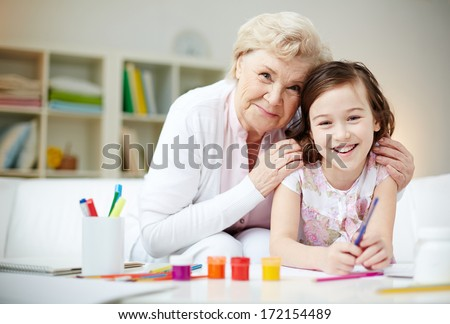 Portrait of happy girl and her grandmother looking at camera at home - stock photo