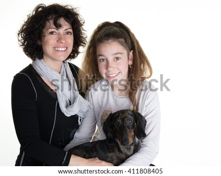 Portrait of happy girl and her mother cuddling dog