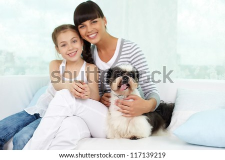 Portrait of happy girl and her mother with shih-tzu dog looking at camera - stock photo