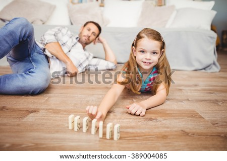 Portrait of happy girl arranging domino by father on hardwood floor at home