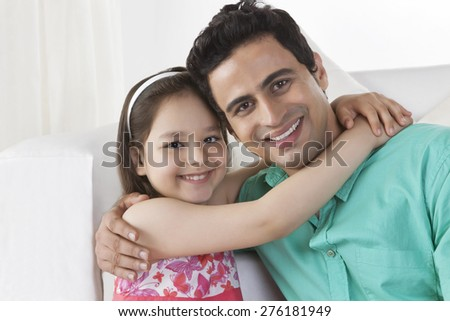 Portrait of happy girl embracing father in house - stock photo