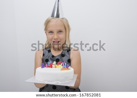Portrait of happy girl holding birthday cake at home - stock photo
