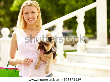 Portrait of happy girl holding pet and looking at camera - stock photo