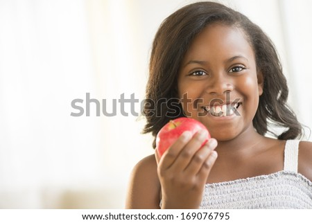 Portrait of happy girl holding red apple at home - stock photo
