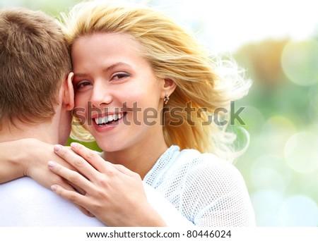 Portrait of happy girl hugging her boyfriend outside - stock photo