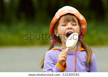 portrait of happy girl in a hat who eats ice cream - stock photo