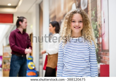 Portrait of happy girl in mall and parents standing behind