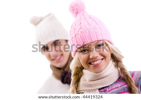 Portrait of happy girl in pink knitted cap on background of her boyfriend