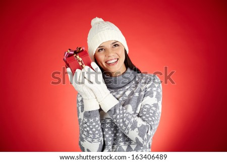 Portrait of happy girl in winterwear holding giftbox by her ear - stock photo