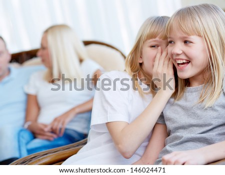 Portrait of happy girl laughing while her twin sister whispering something to her - stock photo