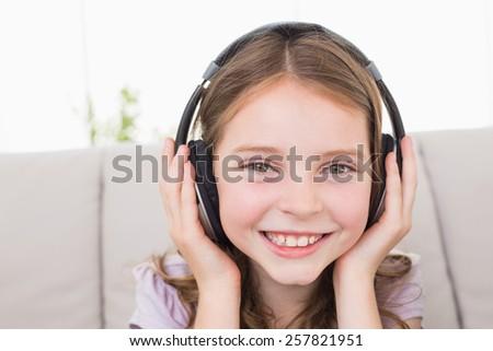 Portrait of happy girl listening music through headphones at home - stock photo