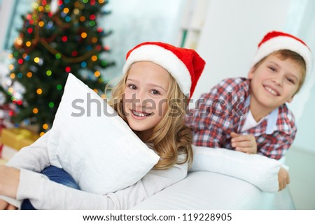 Portrait of happy girl looking at camera with her brother on background on Christmas evening