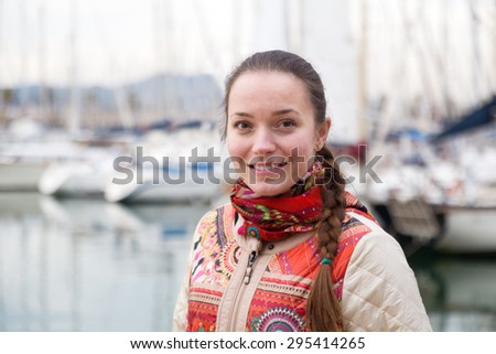 Portrait of happy girl outdoors with yachts at background - stock photo