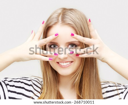 Portrait of happy girl  peeking through fingers at the camera. Studio shot, grey background. - stock photo