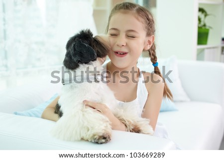 Portrait of happy girl playing with shih-tzu dog at home - stock photo