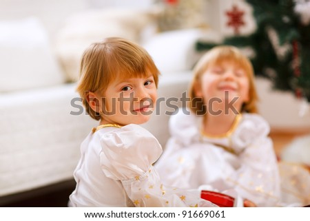 Portrait of happy girl playing with sister near Christmas tree