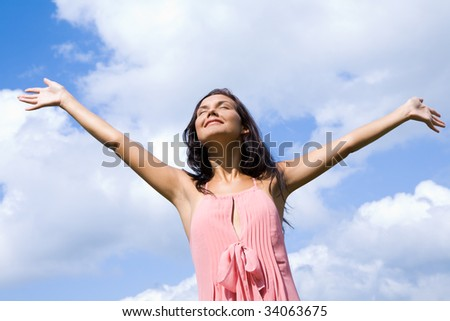 Portrait of happy girl praising God with her eyes shut and raised arms on background of cloudy sky - stock photo