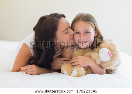 Portrait of happy girl receiving kiss from mother while lying in bed at home - stock photo