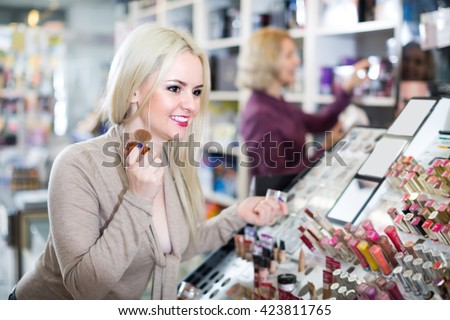 Portrait of happy girl selecting face powder in beauty store