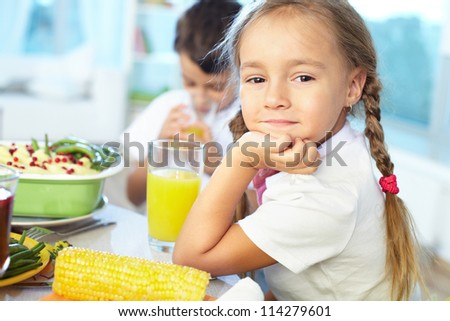 Portrait of happy girl sitting at festive table and looking at camera - stock photo