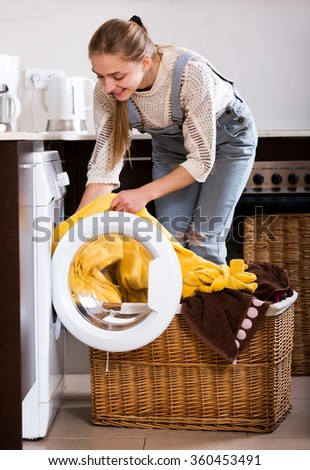 Portrait of happy girl taking clothes out washing machine at home - stock photo