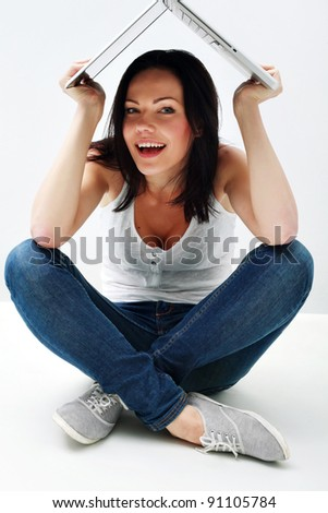 Portrait of happy girl that hiding behind the laptop - stock photo