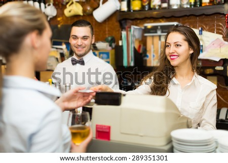 Portrait of happy girl with barman at counter. Focus on girl