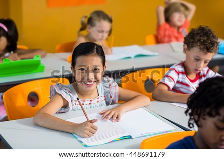 Portrait of happy girl with book on bench in classroom