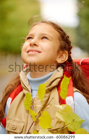 Portrait of happy girl with dry linden branch looking upwards on autumnal day - stock photo