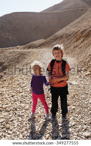 Portrait of happy girl with her autistic brother traveling outdoors - stock photo
