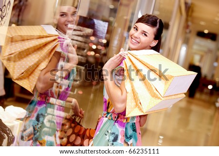 Portrait of happy girl with paper bags looking at camera in the mall - stock photo