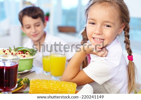 Portrait of happy girl with pigtails looking at camera on background of her brother - stock photo