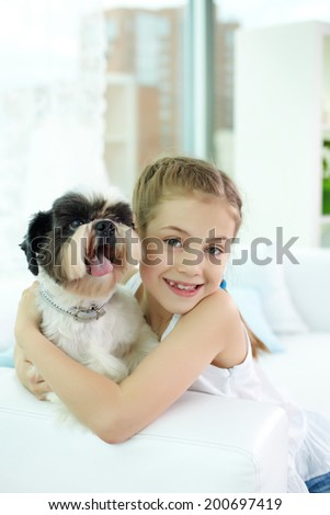 Portrait of happy girl withshih-tzu dog and looking at camera - stock photo