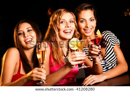 Portrait of happy girlfriends holding martini glasses with cocktails - stock photo
